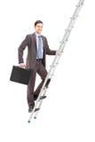 Full length portrait of a businessman climbing a ladder Stock Image