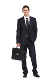 Full-length portrait of businessman handing briefcase Royalty Free Stock Photography