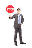 Full length portrait of a businessman holding a stop sign Stock Photo