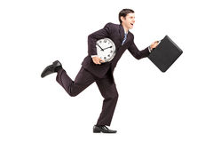 Full length portrait of a businessman running with clock and bri Royalty Free Stock Photo