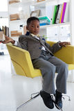 Full length portrait of businessman sitting on armchair. In office Stock Images