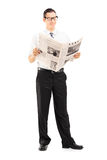 Full length portrait of a businessman standing and reading a new Stock Photography