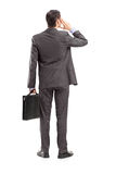 Full length portrait of a businessman thinking, shot from behind Royalty Free Stock Photo
