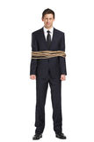 Full-length portrait of businessman tied with the rope. Isolated on white. Concept of slavery and violence Royalty Free Stock Images