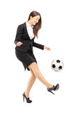 Full length portrait of a businesswoman in high heels kicking a. Soccer ball isolated on white background stock photography