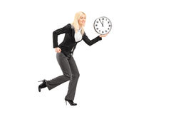 Full length portrait of a businesswoman running with clock Stock Photos