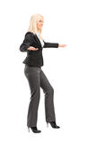 Full length portrait of a businesswoman trying to keep balance. Isolated on white background Stock Photography