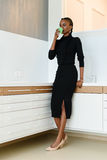 Full length portrait of a businesswoman wearing black dress and beige shoes drinking coffee while working at light office Stock Photo
