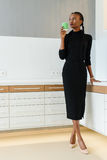 Full length portrait of a businesswoman wearing black dress and beige shoes holding disposable cup looking towards Royalty Free Stock Photos