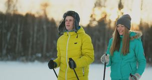 Full length portrait of caring young man helping injured girlfriend during ski walk in winter forest.  stock video