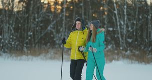 Full length portrait of caring young man helping injured girlfriend during ski walk in winter forest stock footage