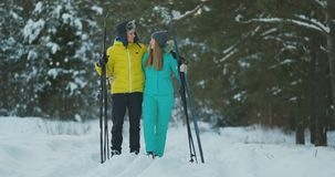 Full length portrait of caring young man helping injured girlfriend during ski walk in winter forest stock video