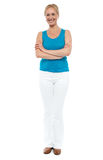 Full length portrait of casual cheerful woman. Posing with arms folded over white background Stock Photos