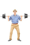 Full length portrait of a casual guy lifting a weight Royalty Free Stock Photography