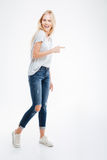 Full length portrait of a casual woman pointing finger away Stock Image