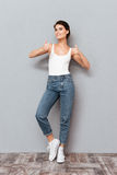 Full length portrait of a casual woman showing thumbs up Royalty Free Stock Photos