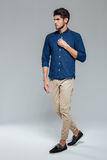 Full length portrait of a casual young man fastening button Stock Photos