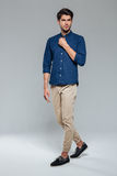 Full length portrait of a casual young man fastening button Stock Image