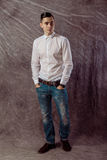 Full length portrait of a casual young man standing with both Stock Photography