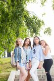 Full length portrait of charming young student girls in the Park in summer. Women wear pastel colored clothes, sneakers and shoes stock photo