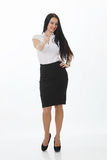 Full length portrait of a cheerful businesswoman pointing finger away camera. Isolated on a white background. Looking at camera Stock Photography