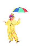 Full length portrait of a cheerful clown holding an umbrella. Full length portrait of a cheerful clown holding a colorful umbrella isolated on white background Royalty Free Stock Image