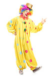 Full length portrait of a cheerful clown in a yellow costume. On white background Stock Photos