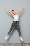 Full length portrait of a cheerful cute woman jumping stock photography