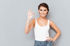 Full length portrait of a cheerful girl showing ok sign Royalty Free Stock Photos