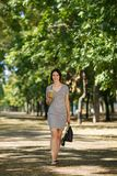 Successful woman in the park. Pretty girl with a cocktail on a natural background. Walking outside concept. Copy space. Stock Photos