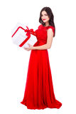 Full length portrait of cheerful woman in red dress with big gif. T box isolated on white background Stock Photos