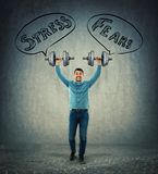 Face your strees and fears. Full length portrait of a cheerful young man lifting up dumbbell weights above his head as facing his fears and stress. Business stock image