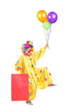 Full length portrait of a cheerfull clown with balloons and pape. R bag, isolated on white background Stock Image