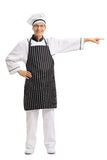 Full length portrait of a chef pointing right Royalty Free Stock Photography