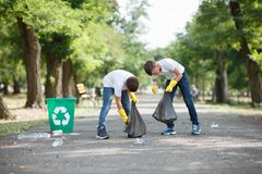 A couple of little boys holding black garbage bags and collecting plastic rubbish on a park background. Ecology. A full-length portrait of children collecting stock photos