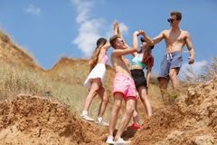 A full-length portrait of a group of teens on a top of a hill gives five each other on a natural blurred background. Royalty Free Stock Images
