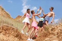 A full-length portrait of a group of teens on a top of a hill gives five each other on a natural blurred background. Stock Photography