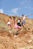 A full-length portrait of smiling young people on a top of a hill gives five each other on a natural blurred background. Stock Photos