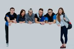 Full length portrait of confident college students displaying blank billboard against white background. Full length portrait of confident college students stock image