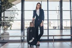 Full-length portrait of confident young business traveler wearing formal suit standing with heavy roll-aboard suitcase. In airport terminal Royalty Free Stock Image
