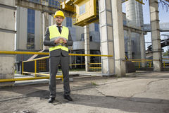 Full length portrait of confident young male architect standing outside industry Royalty Free Stock Images