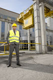 Full length portrait of confident young male engineer standing outside industry Stock Photos