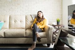 Beautiful Hispanic Woman Relaxing In Living Room. Full length portrait of confident young woman sitting on sofa at home stock photo
