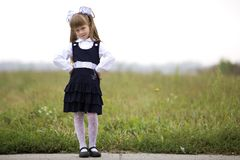 Full-length portrait of cute adorable serious thoughtful first grader girl in school uniform and white bows in long blond hair on. Blurred light green sunny royalty free stock images