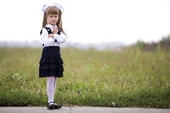 Full-length portrait of cute adorable serious thoughtful first grader girl in school uniform and white bows in long blond hair on. Blurred light green sunny stock photography