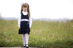 Full-length portrait of cute adorable serious thoughtful first grader girl in school uniform and white bows in long blond hair on. Blurred light green sunny stock image