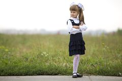 Full-length portrait of cute adorable serious thoughtful first grader girl in school uniform and white bows in long blond hair on. Blurred light green sunny stock photos