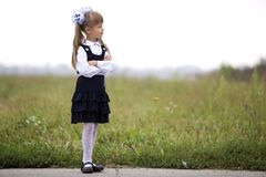 Full-length portrait of cute adorable serious thoughtful first grader girl in school uniform and white bows in long blond hair on. Blurred light green sunny royalty free stock photo