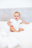 Full length portrait of cute baby sitting on bed Royalty Free Stock Photos