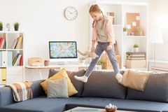 Playful Girl Jumping on Couch stock images